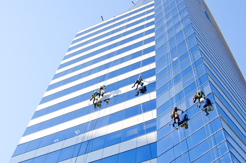 12920814 - group of workers cleaning windows of a tall building at santiago de chile
